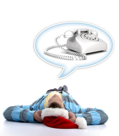 laying man with christmas hat watching telephone in speech bubble photo