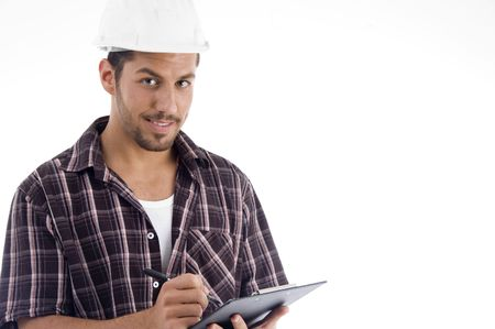engineer writing on pad and looking at camera on an isolated white background