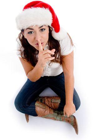 guardar silencio: mujer con sombrero de navidad y pidiendo a guardar silencio sobre un aislado fondo