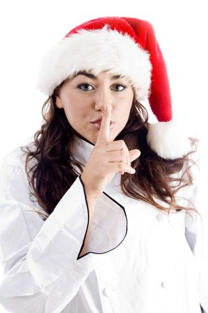 shushing: pretty chef wearing christmas hat and shushing with finger on an isolated background Stock Photo