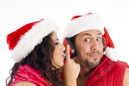shushing: loving american couple wearing christmas hat and woman shushing on an isolated background