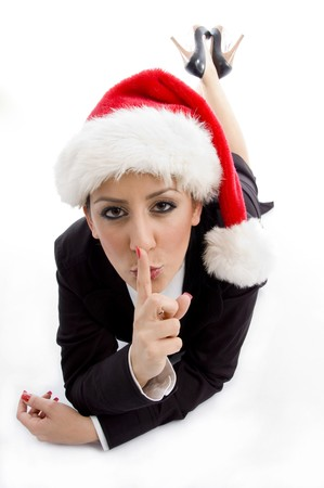 businesswoman with christmas hat instructing to keep silent  on an isolated white background photo