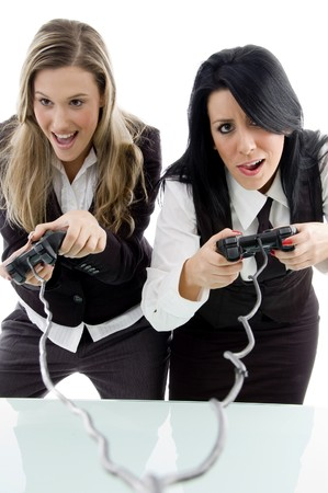 financial controller: female partners playing game and holding remote against white background Stock Photo