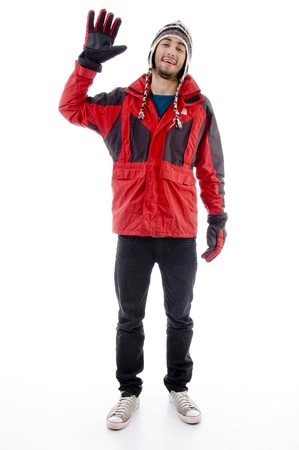 21: man wearing winter cap and jacket waving hello against white background