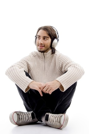 young handsome male listening to music with headphones against white background photo