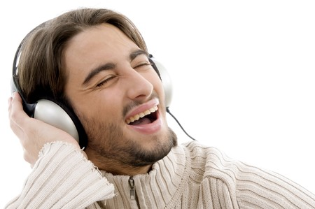 young handsome male listening to music with headphonesagainst white background photo