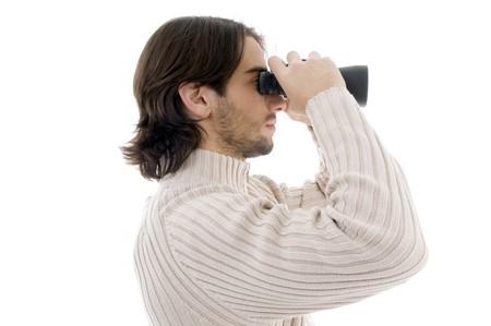 side pose: parte de los j�venes plantean el hombre mirando a trav�s de un binocular sobre fondo blanco aisladas Foto de archivo