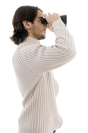 side pose: plantean lado de los j�venes de sexo masculino mirando a trav�s de un binocular sobre antecedentes aislados Foto de archivo