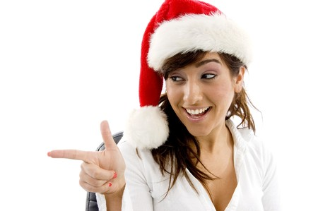 front view of smiling businesswoman in christmas hat pointing sideways against white background photo