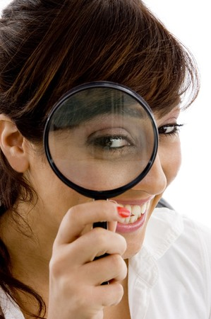 front view of smiling female holding magnifier close to eye on an isolated white background