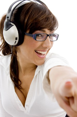 front view of smiling businesswoman pointing with headphones  on an isolated background photo