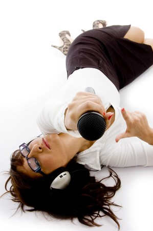 high angle view of businesswoman lying down holding a microphone against white background photo