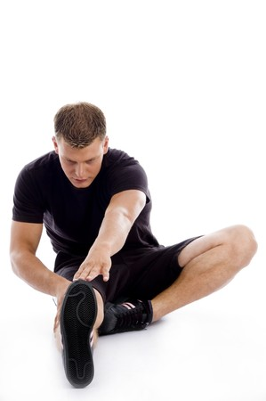 muscular man stretching his legs and hands on an isolated white background photo