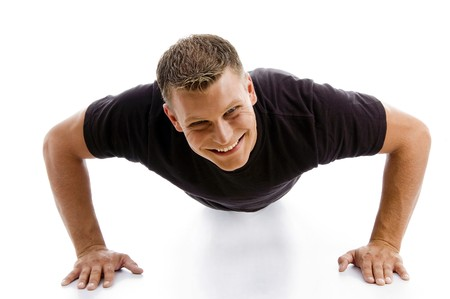 smiling muscular male doing push ups against white background photo