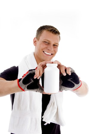 smiling muscular guy showing medicine bottle on an isolated background photo