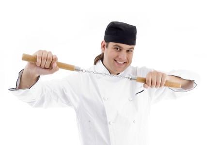nunchaku: chef posing holding nunchaku on an isolated white background
