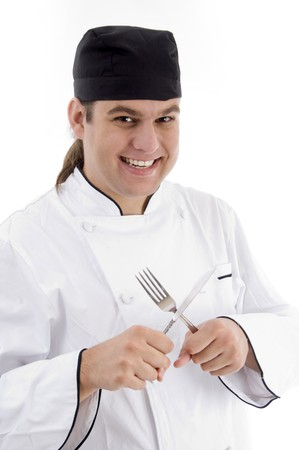 smiling young male chef holding fork and knife on an isolated white background photo