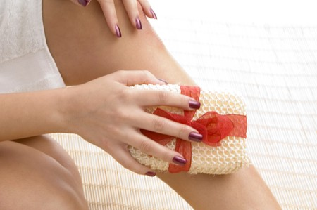 scrubber: close up of young womans leg with scrubber with white background