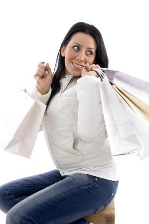 side pose: plantean de cara sonriente mujer con bolsas de la compra en un aislado fondo blanco Foto de archivo