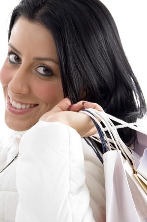 side pose: plantean de cara sonriente mujer llevando bolsas de la compra con el fondo blanco