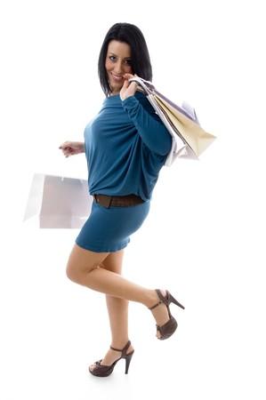 side pose: plantean de cara sonriente modelo de la celebraci�n de llevar las bolsas con fondo blanco Foto de archivo