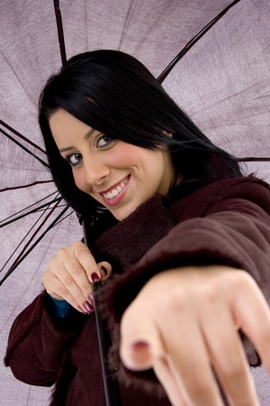front view of pointing woman holding umbrella on an isolated white background photo