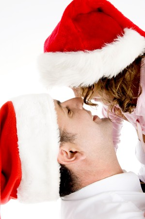 father and daughter wearing santa hat playing against white background photo
