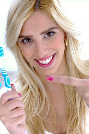 front view of smiling woman pointing at toothbrush against white background photo