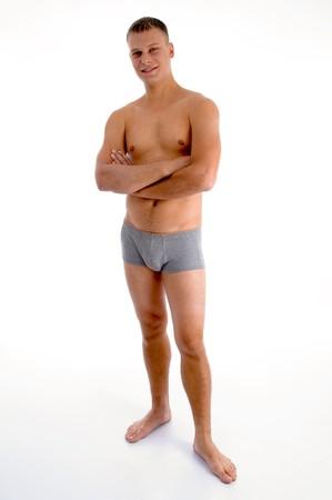 wit ondergoed: permanente gespierde man met gekruiste armen op een geïsoleerde witte achtergrond Stockfoto
