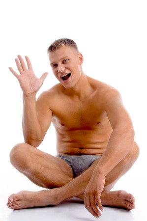 one mature man only: sitting muscular male showing palm on an isolated background