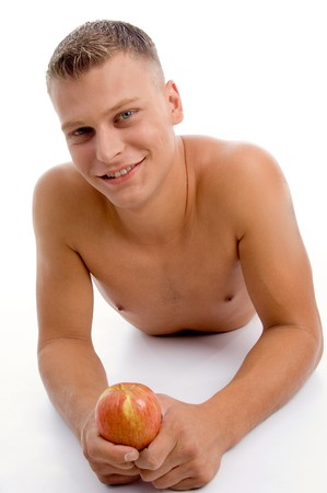 laying fit guy with apple on an isolated white background photo