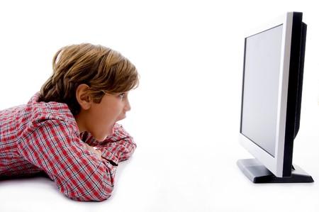 side pose: plantean lado de ni�o viendo la pantalla LCD contra el fondo blanco Foto de archivo