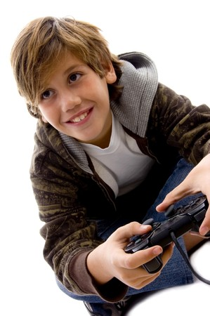 10s: side view of amused boy playing videogame against white background