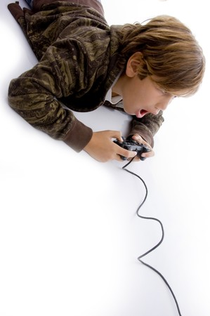 10s: high angle view of amazed boy playing videogame against white background