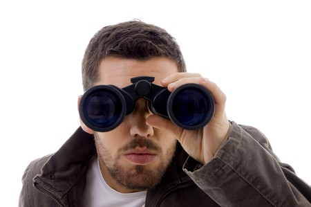 front view of serious male viewing through binoculars against white background Standard-Bild
