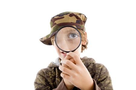 portrait of little boy looking through lens against white background Standard-Bild
