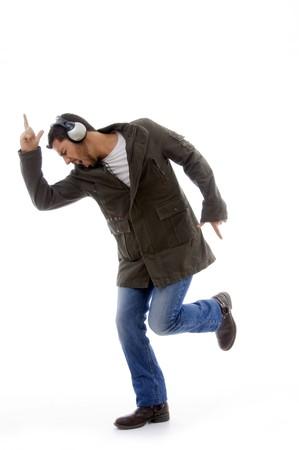 side view of man enjoying music against white background photo