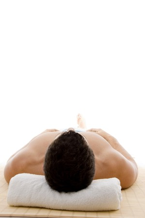 front view of man lying down for spa treatment on an isolated background photo