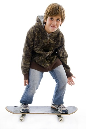 10s: front view of smiling child standing on skateboard on an isolated background