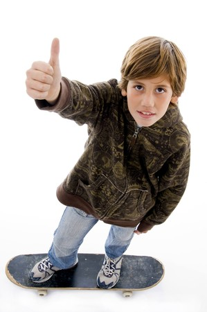 ten year old: top view of boy riding skateboard and showing thumbs up on an isolated white background Stock Photo