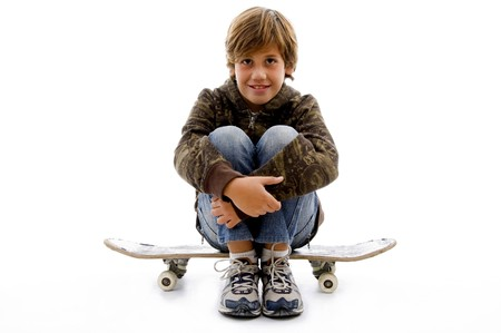 front view of boy sitting on skateboard on an isolated white background photo