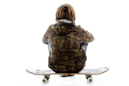10s: back pose of boy sitting on skateboard with white background Stock Photo