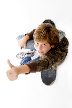 top view of boy sitting on skateboard and showing thumbs up on an isolated white background Standard-Bild