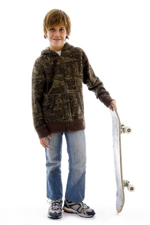 10 year old: front view of boy holding skateboard against white background