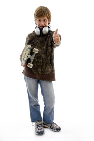 front view of boy holding skateboard and showing thumbs up on an isolated white background photo