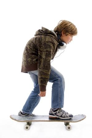 side pose: plantean de cara muchachito montar patineta contra el fondo blanco Foto de archivo
