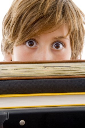 10s: eyelevel view of boy with books against white background Stock Photo