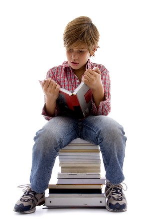 front view of boy sitting on books with white background Standard-Bild