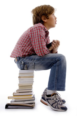 top view of boy sitting on stack of books with white background photo