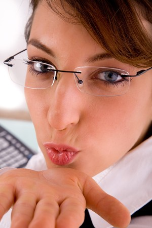 flying kiss: front view of female executive blowing flying kiss  in an office